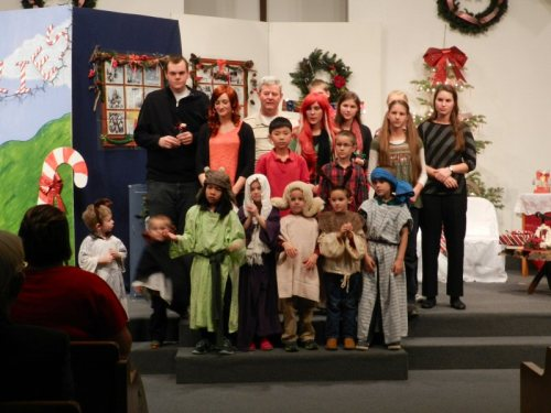 Cast and children's choir sing We Wish You A Merry Christmas