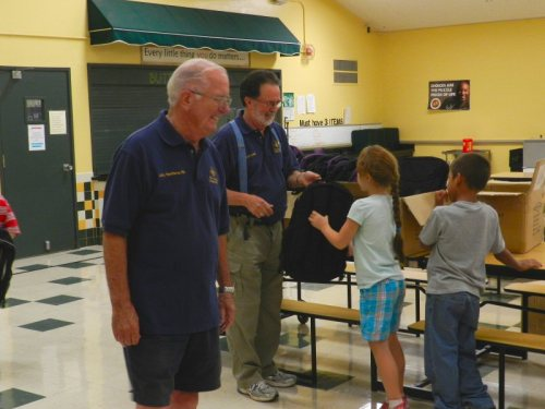 Larry Hawthorne and Jim Crockett give backpacks to Burney 2nd graders