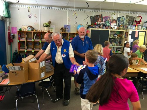 Rotary Club members handing out dictionaries at Fall River Elementary School