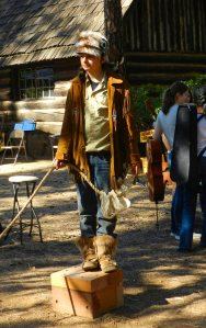 Teen in buckskins and a raccoon hat with three tails