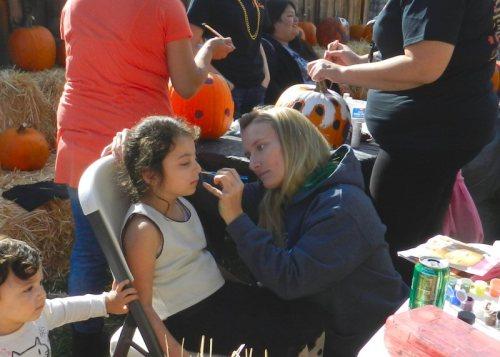 Burney High Senior Megan Arsenau face painting a child
