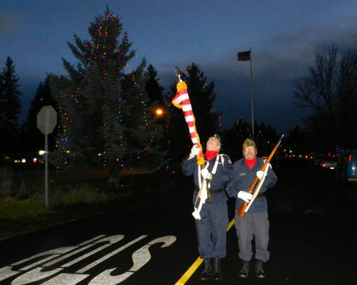 Two of the honor guard with the newly lit trees in the background